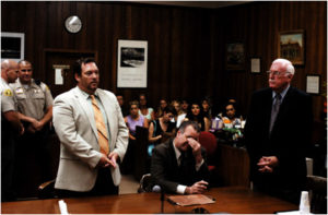 Возле маньяка Уэйна Адама Форда стоят его адвокаты.
