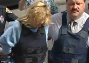 Соучастница Дина Долорес Райли в сопровождении полицейских.