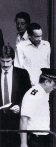 Серийный убийцаКеннет Эрскин в сопровождении полицейских.