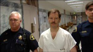 Серийный убийца Гэри Леон Риджуэй в сопровождении полицейских.