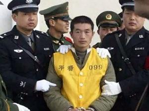 Китайский маньяк Ян Синьхай под конвоем.