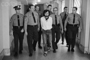 Маньяк Чарльз Мэнсон признанный виновным в семи убийствах в сопровождении полицейских.