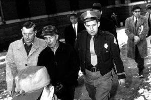 Маньяк Эдвард Гейн в сопровождении полицейских.