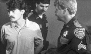 Маньяк Уэстли Додд в сопровождении полицейских.